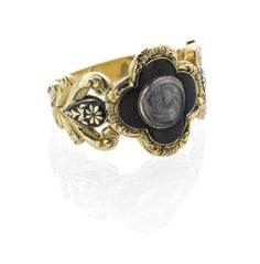 A memorial ring, second quarter of the 19th century The head of quatrefoil design, the central glazed locket compartment set with hair, surrounded by black enamel, the scrolling openwork shoulders with floral decoration and black enamel accents, the hoop reeded, engraved inside head 'Sir Wm Forbes/Died 24th October 1828/Aged 56'