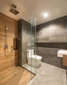 This modern bathroom uses a mixture of grey tiles, wood, and glass, to create a calm experience. Grey Bathroom Tiles, White Bathroom, Small Bathroom, Grey Tiles, Bathroom Ideas, Shower Tiles, Wood Tiles, Bathroom Renovations, Serene Bathroom