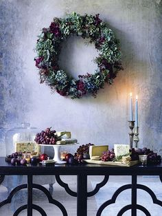 Cheese and fruit artfully presented on wooden boards, cake stands and under glass domes bring to mind a still life, with the grapes echoing the wreath's crimson hues. Homes & Gardens. http://www.hglivingbeautifully.com/2015/12/17/food-for-friends-a-feast-for-the-senses/