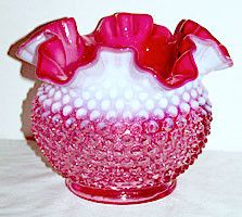 This is a very pretty cranberry opalescent vase in the hobnail pattern that was made by Fenton. It stands 5 inches tall by 6.5 inches wide and is not marked. This vase is in very nice condition with n