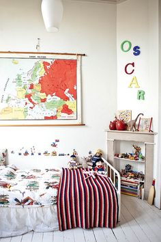 white walls aren't boring with a bright map on the wall and colorful bedding and toys in a little boys room: by decor8, via Flickr
