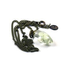 Collier pendentif goutte aplatie en résine transparente avec inclusions de fleurs blanches pressées et séchées.