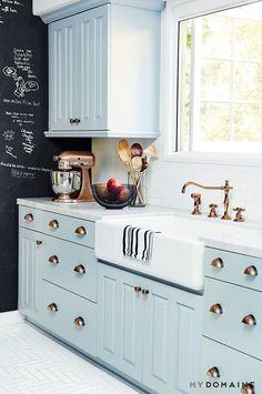 seafoam colored cabinets, farmhouse sink, brass hardware, chalkboard wall