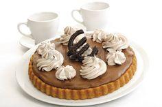 Bizcocho de chocolate con el signo del euro y dos tazas de café LANG_EVOIMAGES