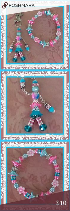 🌺🌴🌺 HANDMADE CHILD'S BACKPACK ACCESSORY 🌺🌴🌺 🌺🌴This handcrafted pair is so much more vibrant and colorful in person.  This little girl has a double layer tulip skirt with silver filigree overlay.  She's wearing pink and silver leggings and brightly colored turquoise shoes.  Her shirt is a pretty shade of pink and blue.  Her outfit is topped off with her blue and white striped hat.  A child's name can be added to the swivel hook.  The bracelet can be altered to fit the child.  Just LMK…