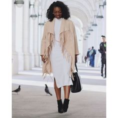 Fringed overpiece over white midi dress with black booties