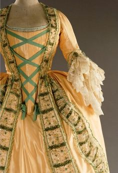 Full dress with horizontal fullness at the hip. The stomacher is attached to the dress. Engageants at the elbow
