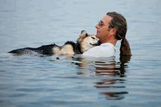 A man held up his old dog friend in the water to ease his joint pain, with the prop of the water buoyancy, he fell asleep in the man's arms.
