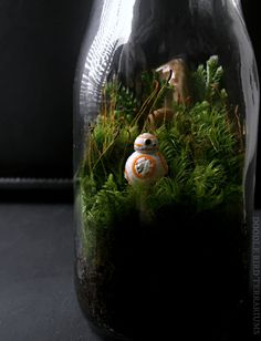Tiny BB-8 replica is housed within a glass milk bottle planted with live moss. The miniature landscape scene will make a unique addition to any Star