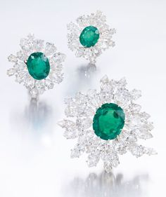 EMERALD AND DIAMOND BROOCH AND A PAIR OF EAR CLIPS, BULGARI. Each of stylised flower design, set to the centre with an oval emerald within a frame of marquise- and pear-shaped diamonds; and a pair of ear clips en suitesimilarly set, each signed Bulgari.
