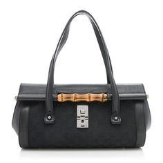 This classic Gucci satchel is made from black GG canvas with tonal leather trim and gunmetal hardware. Details include two flat handles, a central bamboo bar accent, and a flip lock closure. The interior is fully lined with one zippered pocket.