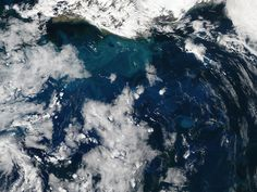A spring bloom of phytoplankton lingered in the Atlantic Ocean off the coast of Iceland in early June, 2014. The Moderate Resolution Imaging Spectroradiometer (MODIS) aboard NASA's Aqua satellite captured this true-color image on June 5. At that time, swirling jewel tones of a vast bloom were visible between banks of white clouds.