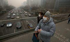 ชาวกรุงปักกิ่งเดินข้ามสะพาน ขณะรถติดบนทางหลวงเบื้องล่าง ท่ามกลางภาวะมลพิษหนาแน่นในอากาศ ซึ่งปกคลุมเมืองหลวงของประเทศจีนเป็นวันที่ 6 ติดต่อกันเมื่อวันอังคาร...