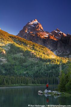 A hiker on Taggart Lake Trail enjoys the sunrise at Taggart Lake,  Grand Teton National Park, Wyoming