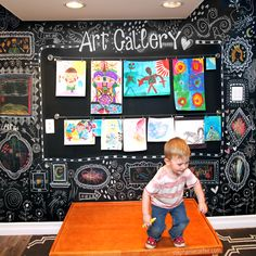 Kids Gallery Wall - We had pre-assembled a bunch of IKEA furniture that would hold art supplies and finished art. We got a large round table and chairs, tabletop easels and paints. And we painted this back wall with chalkboard paint, then hung the cables with clips (also from IKEA) to display art.