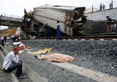 An injured man sits next to the body of a victim following a train accident near the city of Santiago de Compostela. A train hurtled off the tracks on July 24 in northwest Spain killing at least 78 passengers and injuring more than 140. (Monica Ferreiros/La Voz de Galicia via AFP/Getty Images)