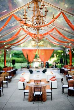 let's do this!  #orange #clear span tent #chandelier reception    I like the addition of the lounge furnishings in the center, and the color draping at the short ends of the ten. dancefloor in the center. Very nice.