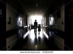 Blur image of a mother and daughter walking on the dark corridor in the hospital.