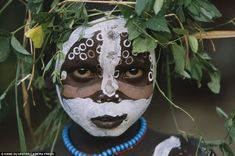Proud: With his painted face and crown of greenery this child is a proud member of one of the tribes who call the Omo Valley in Ethipia home