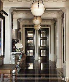 In the entry hall of a Chicago apartment designed by Jean-Louis Deniot, oak doors inset with antiqued mirror lead to the kitchen and private quarters; the pendant lights are by Vaughan, and the leather-and-forged-iron benches were custom made.Pin it. Chicago Apartment, Architectural Digest, Style At Home, Architecture Design, Halls, Interior Design Minimalist, Classic Interior, Design Apartment, Table Design
