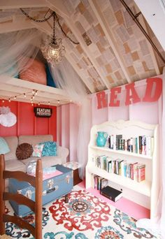 The ceiling is lined with book pages, tulle hangs from above to add softness, and a full bookshelf and bright rug add color and texture to the tiny space.