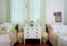 A simetria das camas é reforçada pelos garden seats floridos de cerâmica que ladeiam a cômoda branca. O efeito ocorre mesmo com a janela descentralizada, que tem cortinas de tecido listrado verde e creme