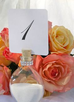 Sand Bottle Table Number Holder. Add a small slit into the cork to hold signage. Custom theme you bottle to have your sand match your wedding colors!