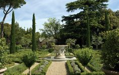 Antique marble fountain rises out of the boxwood parterre.