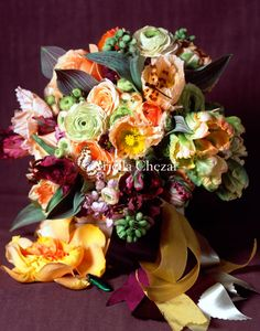 an orange burgundy peach and black bouquet with interesting texture including poppies, ranunculus, and lady slipper orchids