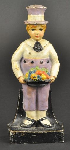 "BOY HOLDING FRUIT BOWL DOORSTOP Heavy casting, very colorful doorstop depicts young boy in top hat presenting bowl of fruit, charming piece, nice mate to ""Girl Holding Flower Basket"". 9 1/4"" h. (Pristine Cond.)"