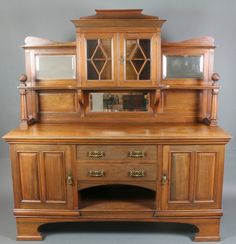 "Lot 866, James Shoolbred Co., An Edwardian Art Nouveau walnut chiffoniere sideboard, the raised mirrored back fitted a cupboard enclosed by astragal glazed doors above 2 long drawers with recess flanked by a pair of cupboards, raised on shaped bracket feet 78""h x 72""w x 24""d, est £150-250"