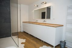 Bathroom with tiles and wood floor and white furniture in Bucharest