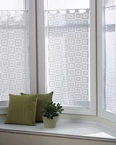 Lacy curtains with a simple geometric blocks-in-blocks pattern. Measure approx. 22.5 x 41.5 ins [57 x 105.5 cm] (excluding tabs). Shown in Bernat Handicrafter Crochet Cotton 00500 White. Size 1.80 mm (U.S. 6) steel crochet hook.
