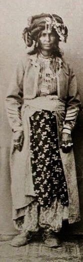 A Kurdish woman from Dersim, in festive outfit, late 19th century.  Ethnic group: probably Zaza and Alevi Kürt.  The Dersim region contains the actual Tunceli province, and some neighbouring districts of the Elazığ and Bingöl provinces.  From a postcard published by the French 'Mission des PP Capucins'.