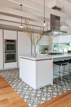 Patterned tile works in place of a rug to define the kitchen. Forsythia branches create a striking, modern arrangement in a cylinder vase. Simple Edison bulb pendant lights serve as minimalist lighting.