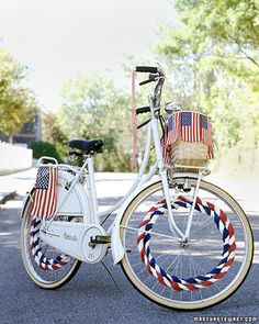 Flags sewn to a length of ribbon encircle the basket of this bike. To decorate the wheels, tape two folds of white crepe paper together into one long piece, roll it up lengthwise, twist snugly, and weave through alternating spokes; make another long twist using blue paper, and then weave it through opposite alternating spokes. Repeat with white and red paper.