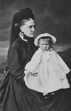 A jovem Princesa Alix de Hesse está sentada no colo da enfermeira usando um vestido de mangas compridas, capa, chapéu. A enfermeira veste o chapéu amarrado com fita debaixo do queixo. Julho de 1873.