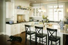 White cabinets, marble island, honed black granite, wood floor, grey walls, blue accents and black lab....PERFECT! by alyce