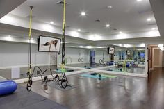 Contemporary basement gym features a tray ceiling accented with pot lighting over mirrored walls and wood floors.