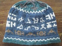 This hat celebrates Stargate: Atlantis. It contains a dart/jumper motif, the glyph address from earth to Atlantis, and a quote from the stairs in Atlantis. The crown of the hat represents Atlantis as seen from above.