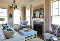 This modest living room represents how furniture placement can change everything! Even though the area is small, there is ample seating. The main couch is centered in front of the statement fireplace. Other seating options include the fabric upholstered ottoman, which can be used as a coffee table, and two elegant wingback chairs.