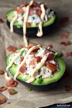 Halved avocados filled with tuna, then topped with crisp bacon and drizzled with…