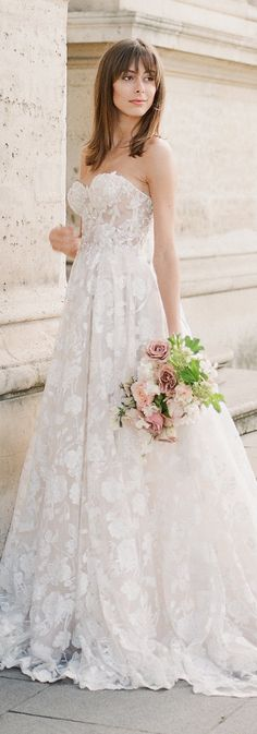 Georgia is a princess ballgown with a sheer corset top embroidered with 3-D flowers and a voluminous pleated skirt with layers of Blush and Ivory silk tulle and flocked tulle with a Victorian Rose pattern made of pearl caviar sequins with Silver accents. #bride #wedding #couture