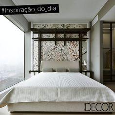Tons neutros compõem o décor do dormitório que inspira conforto. Destaque para a moldura da parede atrás da cama com estampa floral e, também, para a estrutura em madeira em torno da cabeceira. No ambiente também há uma parede em vidro que possibilita a contemplação.