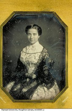 A pretty young lady from Philadelphia. She's wearing a separate top from the neckline of the dress up to a proper daytime neckline, perhaps to make an evening gown modest enough for more public wearing.  The lace shawl is lovely, and was likely brightly colored.  She's also wearing long lace fingerless gloves.  If she knit the lacework herself, she's showing off a real skill.