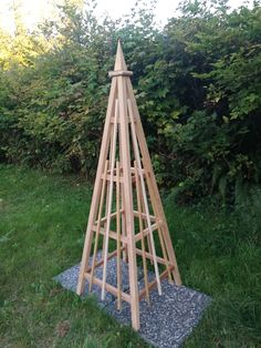"""Red cedar 6' garden tower with 24"""" base. This obelisk is very sturdy and will hold in excess of 400lbs of foliage. It is availble with a spire finial or sphere finial. Great for climbing plants or vegetable tower for cucumbers, peas or squash. Easy assembly with stainless steel hardware."""