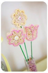 rice krispie treats shaped like flowers with a little royal icing decoration and a green popcicle stick