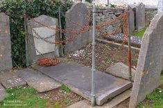 This rather strange grave brings many visitors to Malew Churchyard and as can be seen by the image it is iron staked at each corner and randomly heavily chained to keep the vampire in!    The Vampire was a Mr Halsall who died aged 54, when he died the Undertakers were not allowed to bring his body onto the consecrated church grounds so rumour has it that they loaded his body into the grave from behind the wall, it was then covered in a heavy slate slab and staked with iron posts and iron…