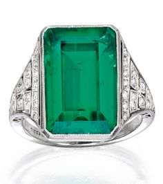 Platinum, Emerald and Diamond Ring, Tiffany & Co. Centring an emerald-cut emerald measuring approximately 15.9 by 10.4 by 6.5 mm, accented by old European-cut diamonds weighing approximately .50 carat, signed Tiffany & Co.; circa 1925.