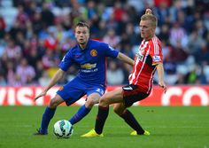 Tom Cleverley of Manchester United is closed down by Sebastian Larsson of Sunderland during the Barclays Premier League match between Sunderland and Manchester United at Stadium of Light on August 24, 2014 in Sunderland, England.